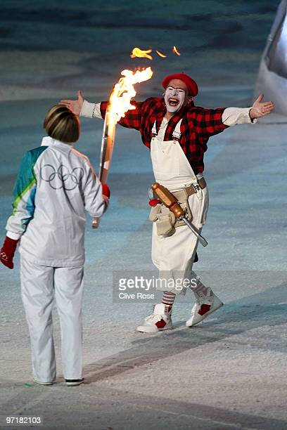 Former speed skater Catriona LeMay Doan holds the Olympic torch as mime Yves Dagenais performs during the Closing Ceremony of the Vancouver 2010...