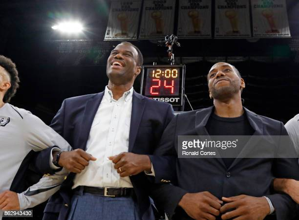 Former Spurs David Robinson joins injured Kawhi Leonard of the San Antonio Spurs during pregame activities before the game against the Minnesota...