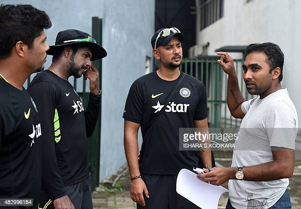 Former Sri Lankan cricket captain Mahela Jayawardene speaks with Indian cricketers Umesh Yadav and Varun Aaron during a practice session at the R...
