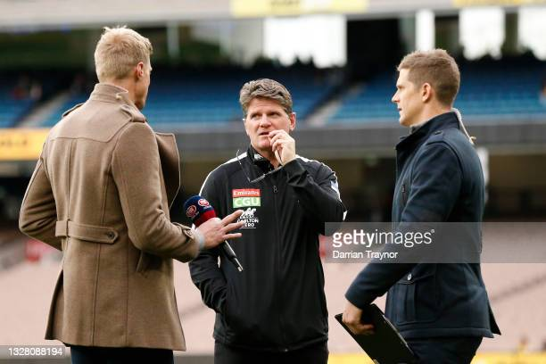 Former St Kilda team mates and now TV personalities Nick Riewoldt and Nick Dal Santo chat with Robert Harvey, Senior Coach of the Magpies before the...