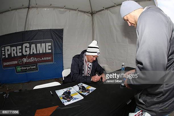Former St Louis Blues player Pierre Turgeon signs autographs for fans at The Pregame prior to the 2017 Bridgestone NHL Winter Classic at Busch...