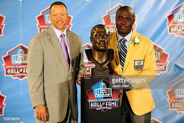 Former St Louis Rams running back Marshal Faulk and his agent Rocky Arceneaux pose with Faulk's bust at the Enshrinement Ceremony for the Pro...