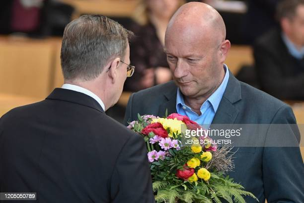 Former state premier Bodo Ramelow of the far left Die Linke party receives flowers from Thomas Kemmerich of the FDP following the election of the...