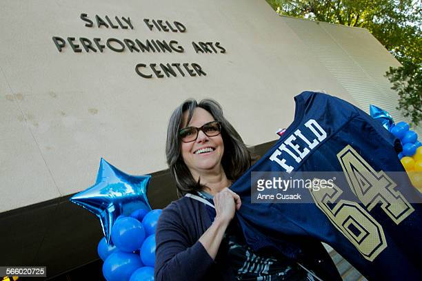 A former student from Birmingham High School Sally Field holds up a jersey given to her as she visits the school in Van Nuys where the Performing...