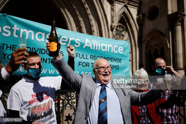 Former subpostmaster at Hogsthorpe, Tom Hedges holds a bottle of champagne aloft outside the Royal Courts of Justice in London, on April 23 following...