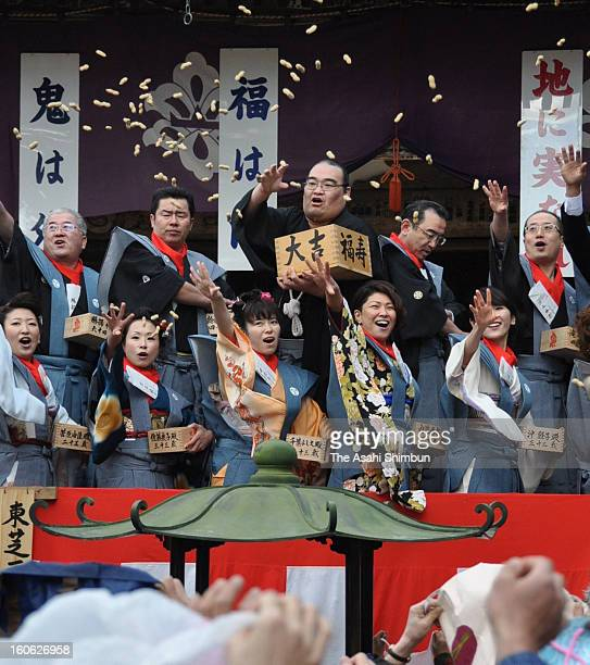 Former sumo wrestler Takamisakari or stable master Furiwake scatters beans during the 'Setsubun' ceremony at Chusonji Temple on February 3 2013 in...