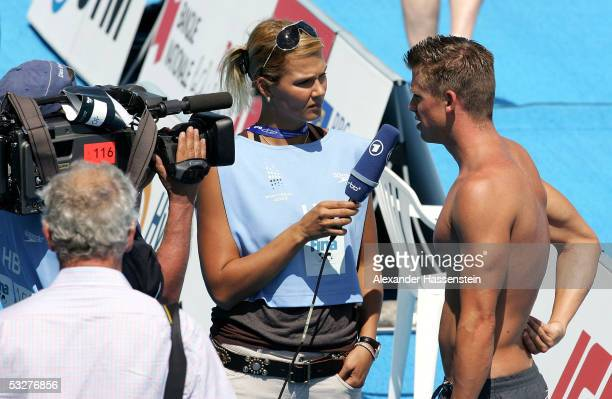 Former swimmer Franziska van Almsick of Germany interviews current swimmer Thomas Rupprath of Germany during a training session before the start of...