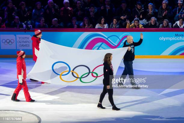 Former Swiss ski champion Didier Cuche waves to the crowd while carrying the olympic flag during Opening Ceremony of the Lausanne 2020 Winter Youth...