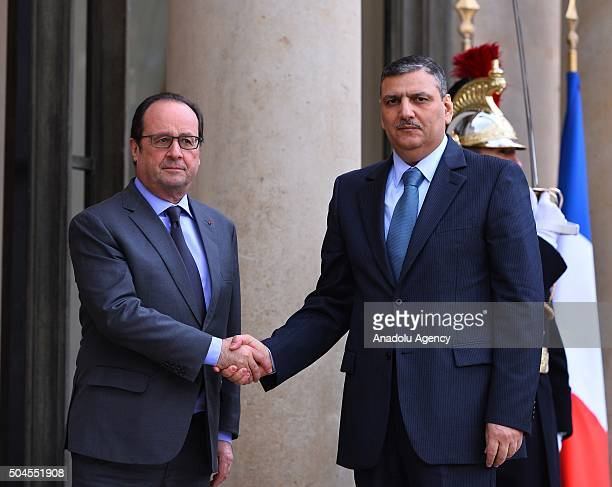 Former Syrian Prime Minister Riyad Farid Hijab shakes hand with President of France Francois Hollande before their meeting in Paris France on January...