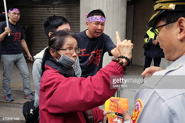 Former Taiwan RCA workers argue with police outside the Pariament during a demonstration in Taipei on April 22 2015 Workers from a factory in Taiwan...