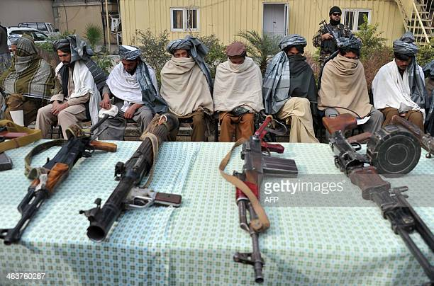 Former Taliban fighters sit alongside their weapons prior to handing them over as they join a government peace and reconciliation process at a...