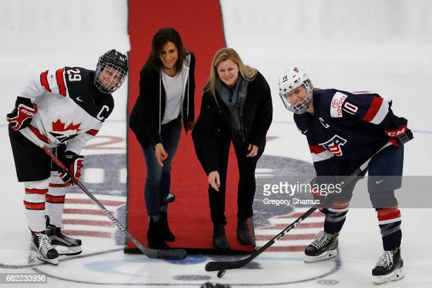 Former Team Canada player Manon Rhaume and Team United States player Shelley Looney drop ceremonial first pucks with Team United States Captain...