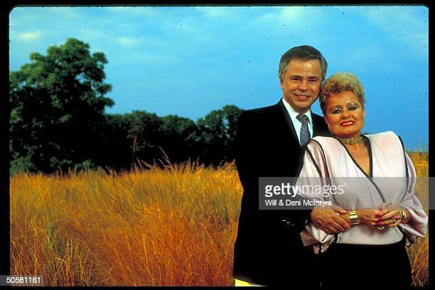Former televangelists Jim and Tammy Faye Bakker in expensively tailored clothes standing in the middle of a wheat field