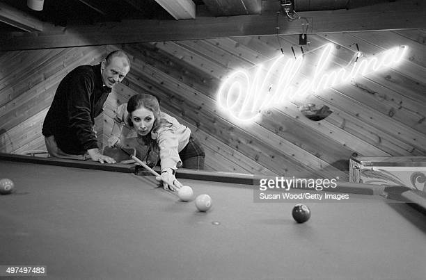Former television producer Bruce Cooper watches as his wife, Dutch-born businesswoman and former model Wilhelmina Cooper lines up a shot at the...