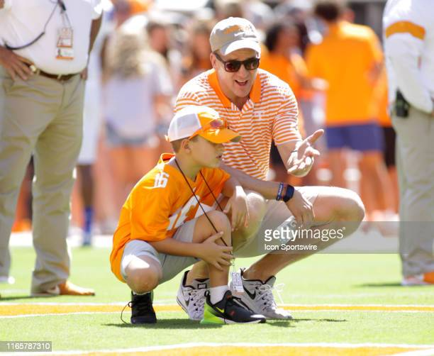 Former Tennessee Volunteers quarterback Peyton Manning watches warmups with his son at midfield prior to a game between the Tennessee Volunteers and...