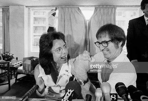 Former tennis great Bobby Riggs and top female tennis player Billie Jean King arm wrestle at a press conference where they announced they'll face...