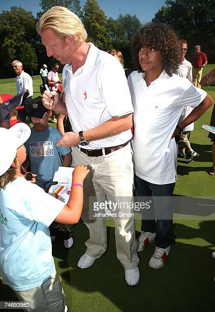 Former Tennis legend Boris Becker writes autographs standing with his son Noah on the grounds during the opening of Hartl Golf resort June 17 2007 in...