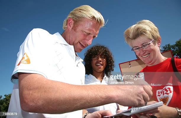 Former Tennis legend Boris Becker writes autographs standing with with his son Noah on the ground during the opening of Hartl Golf resort on June 17...
