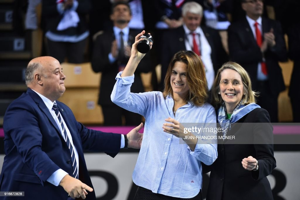 Former tennis player and former France's Fed Cup tennis coach, Amelie Mauresmo (C) reacts after she received from French Tennis Federation (FFT) President, Bernard Giudicelli (L) a prize for her 20 years of commitment to tennis, before the Fed Cup World Group first round tennis match between France and Belgium in Mouilleron-le-Captif, northwestern France, on February 11, 2018. MONIER