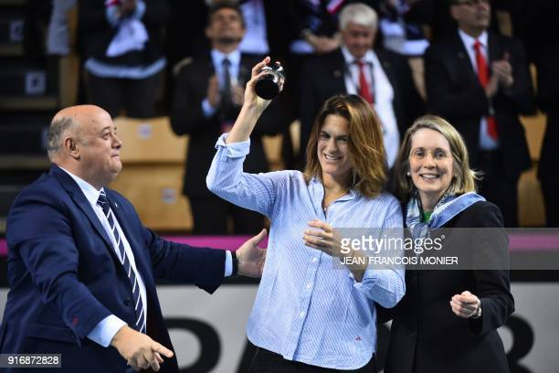 Former tennis player and former France's Fed Cup tennis coach Amelie Mauresmo reacts after she received from French Tennis Federation President...