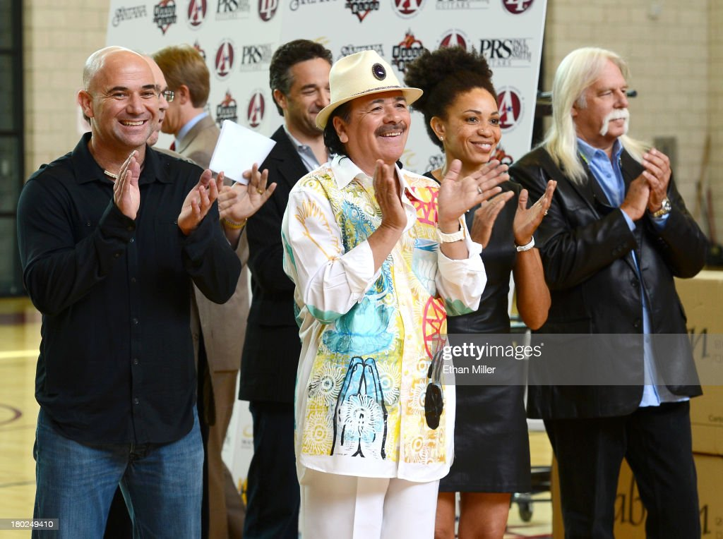 Former tennis player Andre Agassi, recording artist Carlos Santana, his wife, drummer Cindy Blackman, and Vice President of Hermes Music U.S. Gregory Morrison watch a musical performance by students as they visit the Andre Agassi College Preparatory Academy to donate more than 200 guitars from Hermes Music and other instruments from LP Music and PRS Guitars for music students on September 10, 2013 in Las Vegas, Nevada. Santana returned to Las Vegas to continue his residency at the House of Blues Las Vegas.