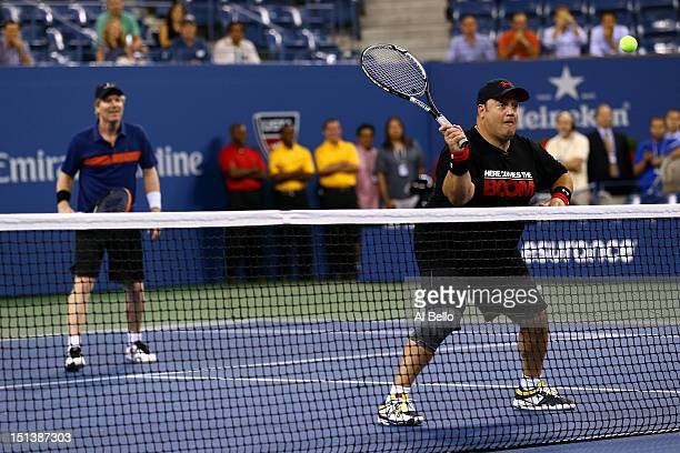 Former tennis player Jim Courier watches as comedian Kevin James returns a shot during a celebrity doubles match on Day Eleven of the 2012 US Open at...