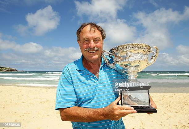Former tennis player John Newcombe poses with the Norman Brookes Challenge Cup during the Australian Open Trophy Tour at Bondi Beach on November 16...