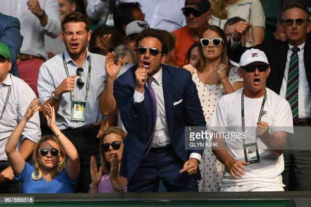 Former tennis player Justin Gimelstrob reacts as he sits in the familly box whilst watching US player John Isner play against South Africa's Kevin...