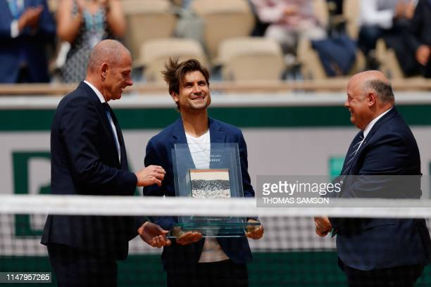Former tennis player Spain's David Ferrer receives an award for his career by President of the French Tennis Federation Bernard Giudicelli and former...
