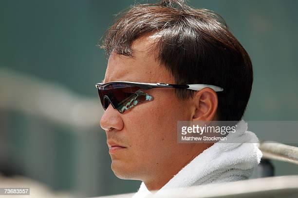 Former tennis star Michael Chang looks on as he watches Ai Sugiyama of Japan, who Chang currently coaches, play Anastasiya Yakimova of Belarus during...
