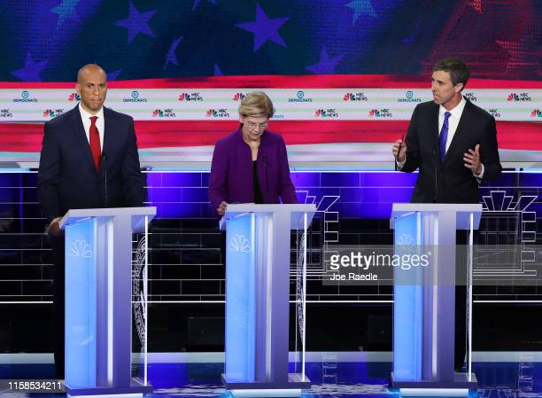 Former Texas congressman Beto O'Rourke speaks as Sen Cory Booker and Sen Elizabeth Warren look on during the first night of the Democratic...