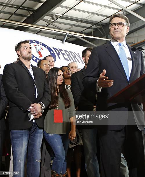 Former Texas Governor Rick Perry speaks as supporters including retired US Navy SEAL and author of the book Lone Survivor Marcus Luttrell stand...