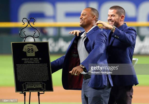 Former Texas Rangers third baseman Adrian Beltre gets a jacket from former teammate Michael Young as he is inducted into the Texas Rangers Hall of...