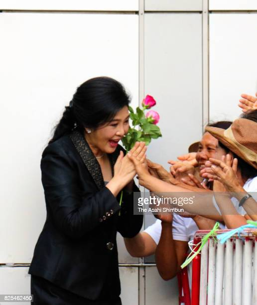 Former Thai prime minister Yingluck Shinawatra greets her supporters on arrival at the Supreme Court on August 1 2017 in Bangkok Thailand