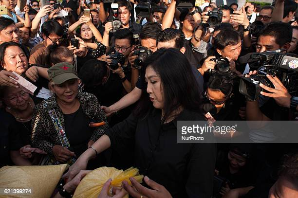 Former Thai prime minister Yingluck Shinawatra hands a bag of rice to one of her supporters outside of a shopping mall in Bangkok Thailand on 5...