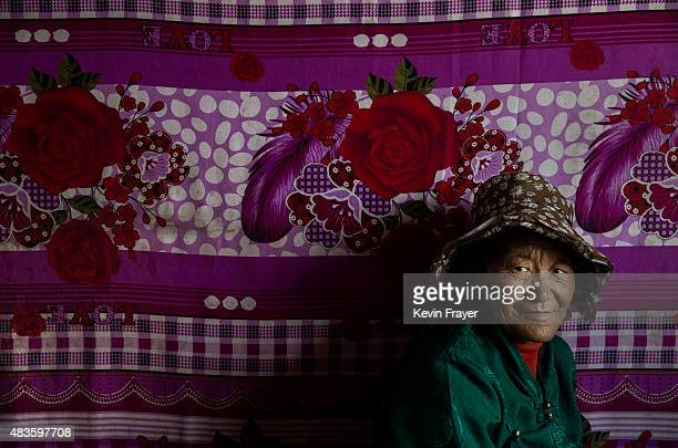 A former Tibetan nomad is seen in the living room of her house in a government resettlement community on July 23 2015 on the Tibetan Plateau in Madou...