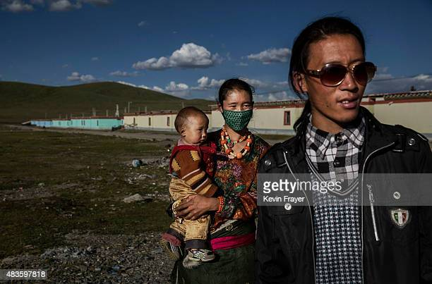 Former Tibetan nomad Kunchuck and wife Sonam stand with their child outside of recently built homes in a government resettlement community for nomads...
