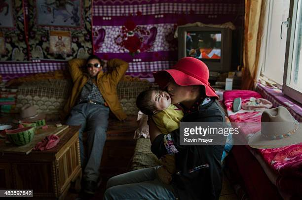 Former Tibetan nomad Kyipotsomo kisses her son Kunchok 3 months as father Jamyang Palden looks on as they sit in the living room of their house in a...