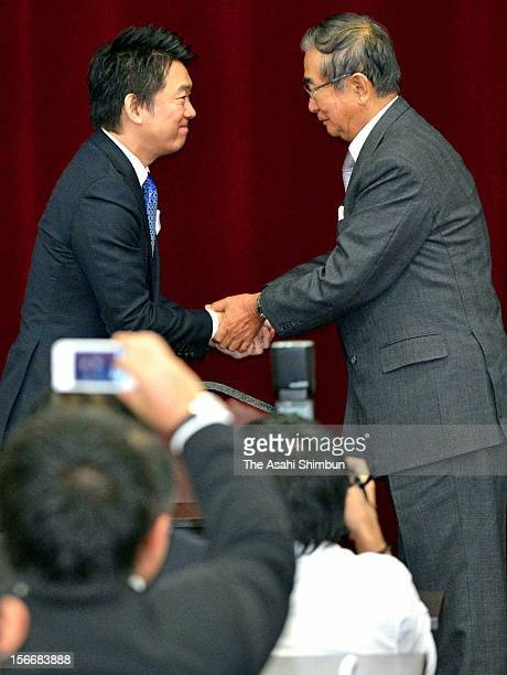 Former Tokyo governor Shintaro Ishihara and Osaka City mayor Toru Hashimoto shake hands at the Japan Restoration Party general meeting on November 17...
