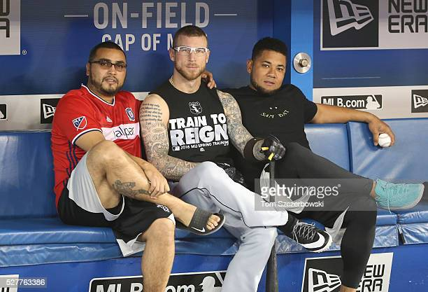 Former Toronto Blue Jays players Dioner Navarro of the Chicago White Sox and Brett Lawrie and Melky Cabrera pose in the visitors dugout before the...