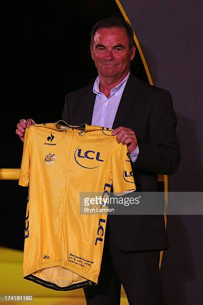 Former Tour winner Bernard Hinault is presented with a commemorative jersey to mark the centinary edition after the twenty first and final stage of...
