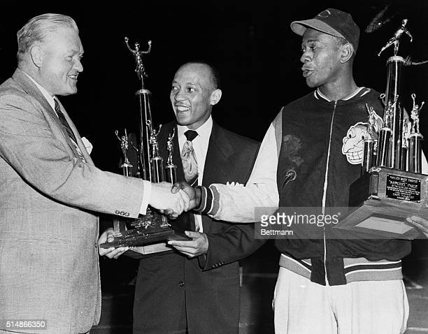 Former track star Jesse Owens and Cleveland Indians' pitcher Satche Paige are congratulated by Illinois States Attorney John Boyle after they...