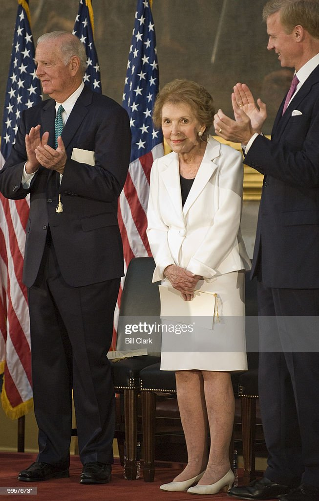 Former Treasury Secretary James Baker, left, and Frederick Ryan, chairman of the Board of Trustees at the Ronald Reagan President Foundation, right clap for former First Lady Nancy Reagan during the ceremony to unveil a statue of former President Ronald Reagan that will become part of the National Statuary Hall Collection on in the U.S. Capitol on Wednesday, June 3, 2009.
