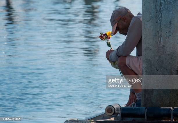 TOPSHOT Former Truth Aquatics crewman James Miranda prays and drops flowers into the water at the moorings where the boat that burned and sank off...