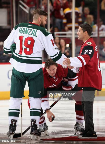 Former Tucson Roadrunners captain Craig Cunningham shakes hands with Martin Hanzal of the Minnesota Wild and Shane Doan of the Arizona Coyotes after...