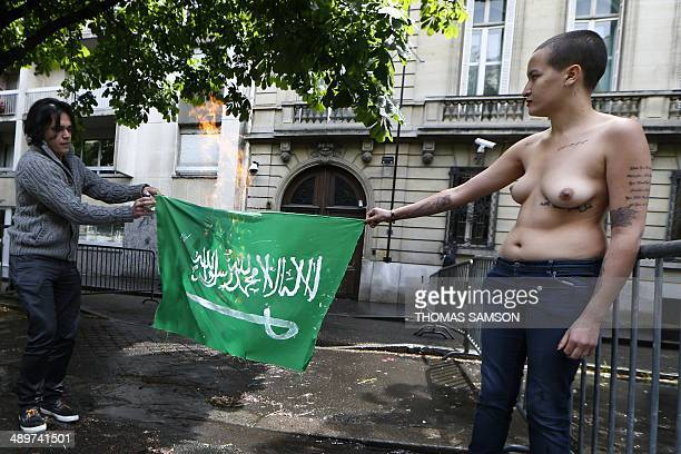 Former Tunisian Femen activist Amina Sboui along with another activist set fire to the Saudi national flag as they demonstrate for the freedom of...