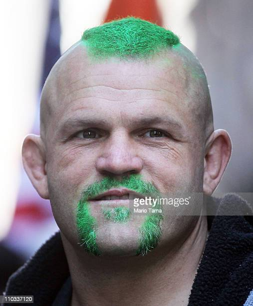 Former UFC Champion Chuck Liddell poses with FDNY firefighters before marching with them at the 250th annual St Patrick's Day parade March 17 2011 in...