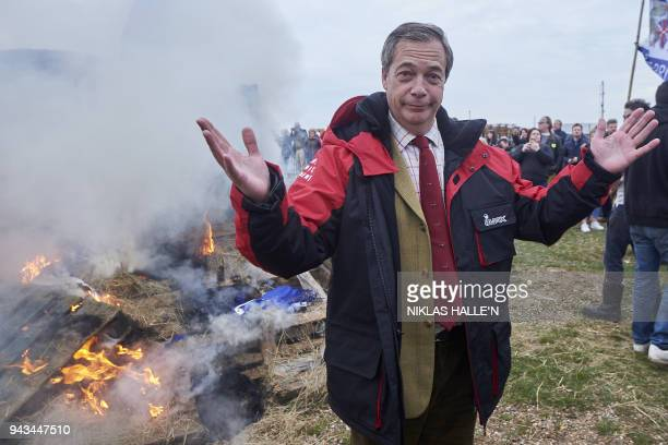Former UK Indepence Party Leader Nigel Farage stands beside the remains of a small boat on top of a bonfire on the shore during a demonstration in...