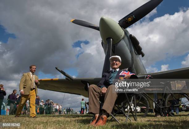 Former UKIP leader Nigel Farage walks past a Spitfire on display as a veteran sits underneath it at the Biggin Hill Festival of Flight on August 19,...