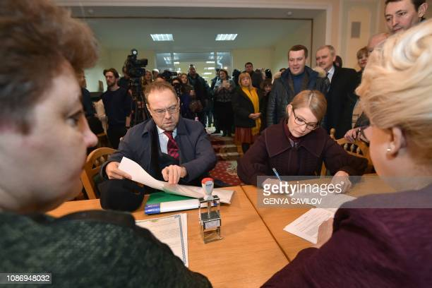 Former Ukrainian Prime Minister Yulia Tymoshenko signs papers as she submits documents to the Ukraines Central Electoral Commission in Kiev on...